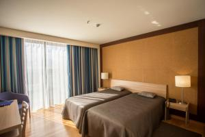 A bed or beds in a room at Antillia Hotel