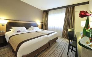 A bed or beds in a room at Mercure Rouen Val de Reuil