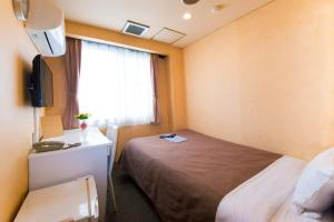 A bed or beds in a room at Hotel Kazusa