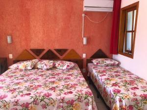 A bed or beds in a room at Pousada do Coqueiro