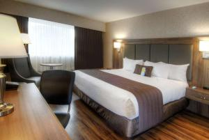 A bed or beds in a room at Days Inn by Wyndham Victoria On The Harbour
