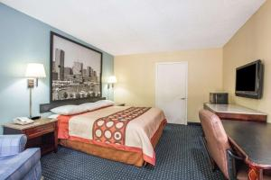 A bed or beds in a room at Super 8 by Wyndham Camp Springs/Andrews AFB DC Area