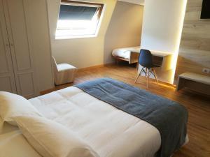 A bed or beds in a room at Hospedium Hotel La Marina Costa da Morte