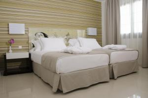 A bed or beds in a room at Boutique Hotel H10 White Suites - Adults Only