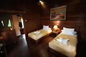 A bed or beds in a room at Mina Tanjung Hotel