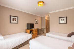 A bed or beds in a room at Best Western Rockingham Forest Hotel