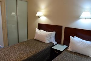 A bed or beds in a room at Lufra Hotel and Apartments
