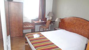 A bed or beds in a room at Logis Cottage Hôtel