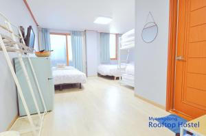 A bed or beds in a room at Myeongdong Rooftop Hostel