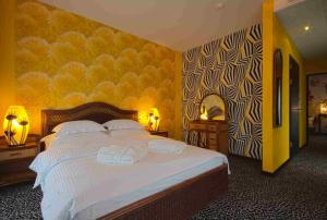 A bed or beds in a room at Hotel Lenart