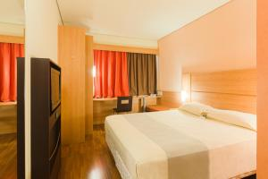 A bed or beds in a room at ibis Canoas Shopping