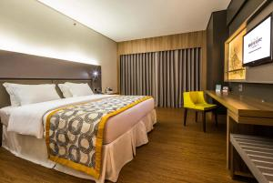 A bed or beds in a room at Mercure Uberlandia Plaza Shopping