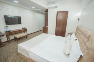 A bed or beds in a room at Plaza Hotel Almaty