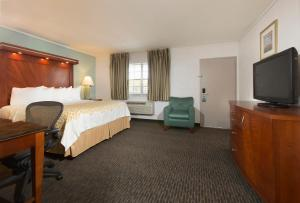 A television and/or entertainment centre at Days Inn by Wyndham Miami Airport North