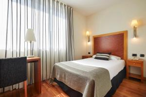 A bed or beds in a room at Exe Plaza Delicias