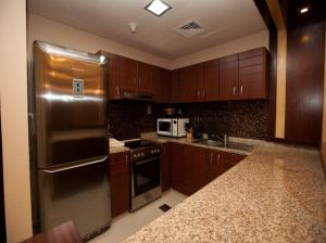 A kitchen or kitchenette at Xclusive Maples Hotel Apartment