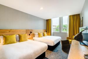 A bed or beds in a room at Apex Grassmarket Hotel