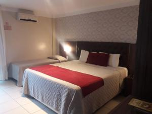 A bed or beds in a room at Hotel Village Premium Caruaru