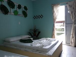 A bed or beds in a room at Pousada Casa Nova