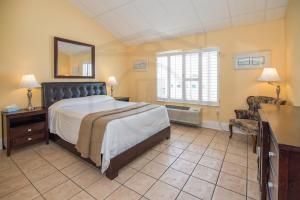 A bed or beds in a room at Naples Park Central Hotel