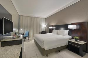 A bed or beds in a room at Hotel Deville Prime Cuiabá
