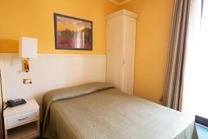 A bed or beds in a room at Cervara Park Hotel
