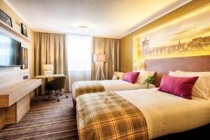 Een bed of bedden in een kamer bij Leonardo Royal Edinburgh Haymarket