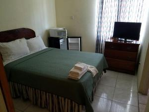 A bed or beds in a room at Tropical Court Resort Near Montego Bay Airport