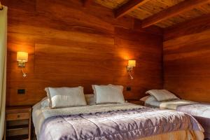 A bed or beds in a room at Olmue Natura Lodge & Spa