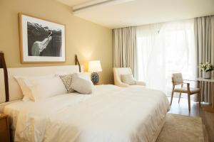 A bed or beds in a room at Domes Miramare, a Luxury Collection Resort, Corfu - Adults Only