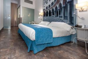 A bed or beds in a room at AACR Hotel Monteolivos