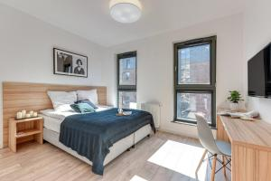A bed or beds in a room at Browar Gdanski Budget by Renters