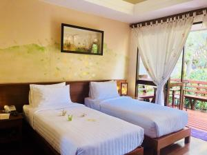 A bed or beds in a room at Baan Duangkaew Resort SHA Plus
