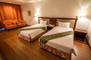 A bed or beds in a room at Tai Pan Hotel