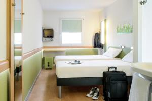A bed or beds in a room at ibis budget Dortmund Airport