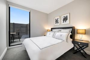 A bed or beds in a room at Manhattan Apartments - Caulfield North