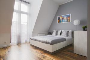A bed or beds in a room at Living Apartments Poznań
