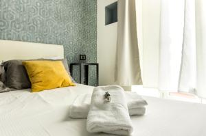 A bed or beds in a room at Merulana 139 Suites