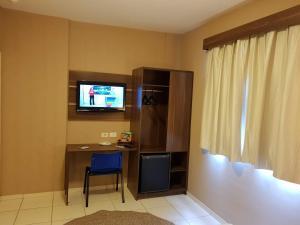 Uma TV ou centro de entretenimento em Astro Hotel