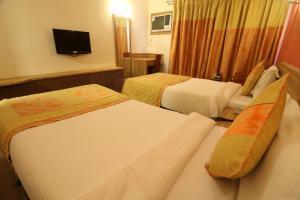 A bed or beds in a room at VITS Kamats Resort, Silvassa