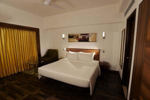 A bed or beds in a room at Lemon Tree Hotel Coimbatore
