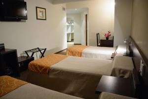 A bed or beds in a room at Hotel Cuatro Plazas