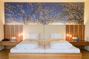 A bed or beds in a room at Genusshotel Riegersburg