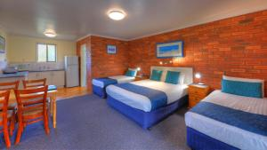 A bed or beds in a room at Pelican Motor Inn