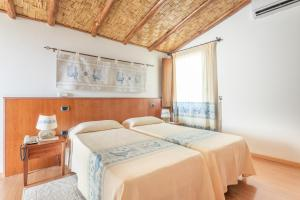 A bed or beds in a room at Hotel Villa Canu