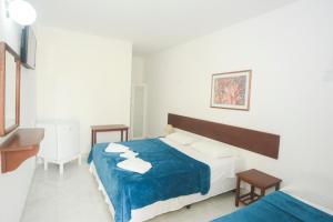 A bed or beds in a room at Pousada Estrela de Paraty