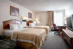 A bed or beds in a room at Days Inn & Suites by Wyndham Denver International Airport