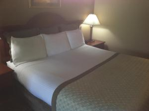 A bed or beds in a room at Hawthorn Suites by Wyndham Napa Valley