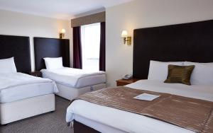 A bed or beds in a room at Raven Hotel by Greene King Inns