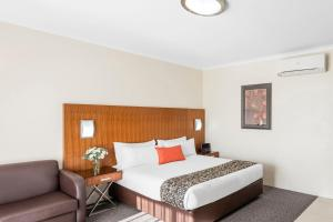 A bed or beds in a room at Central Motel & Apartments, Best Western Signature Collection